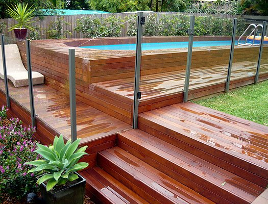 Above Ground Swimming Pool Design With Brick Deck And Glass Fence